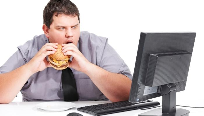 A man eating a burger in front of his desk, learn how to better your wellness programs on the blog!