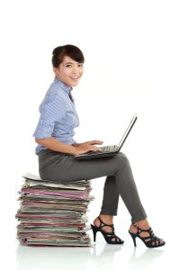Attractive smiling young business woman using laptop sitting on her paperwork